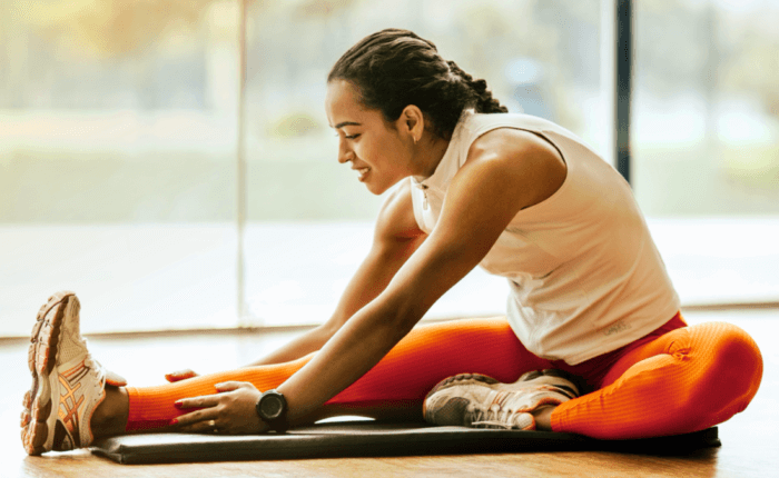 A woman stretches her legs on a yoga mat