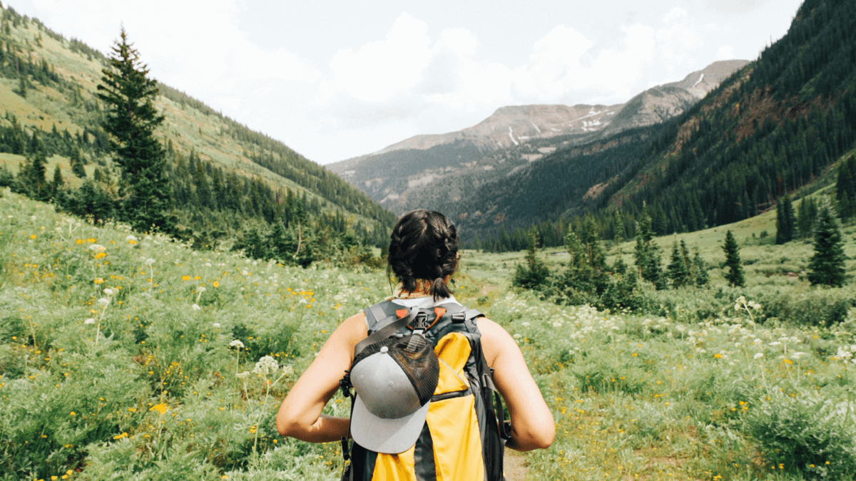 A woman stands with her back to the camera, hiking towards a gorgeous mountain landscape