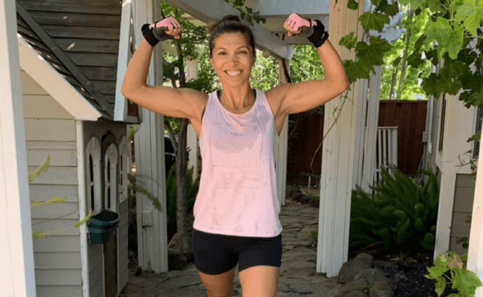 Nobella is standing by her yoga mat after a workout, flexing her muscles and beaming a proud smile.
