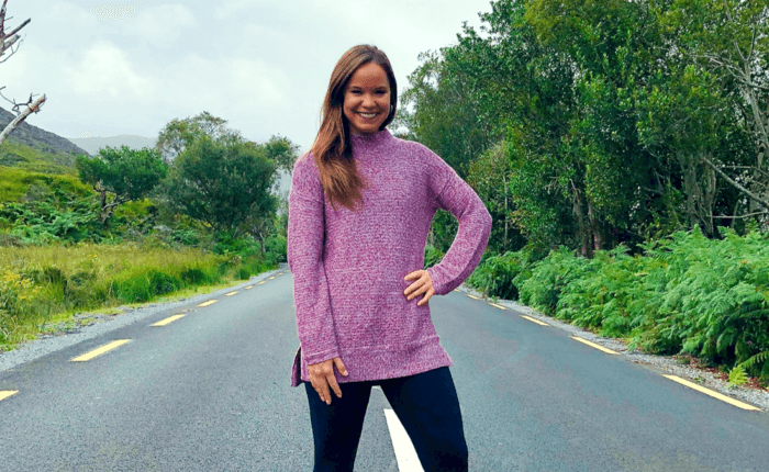 Rebecca Morris, our featured community member, stands proudly in the middle of a road surrounded by greenery.