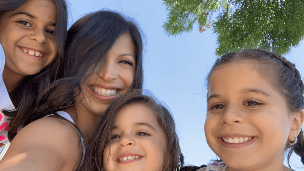 Nobella is surrounded by her three daughters with beautiful, beaming smiles.