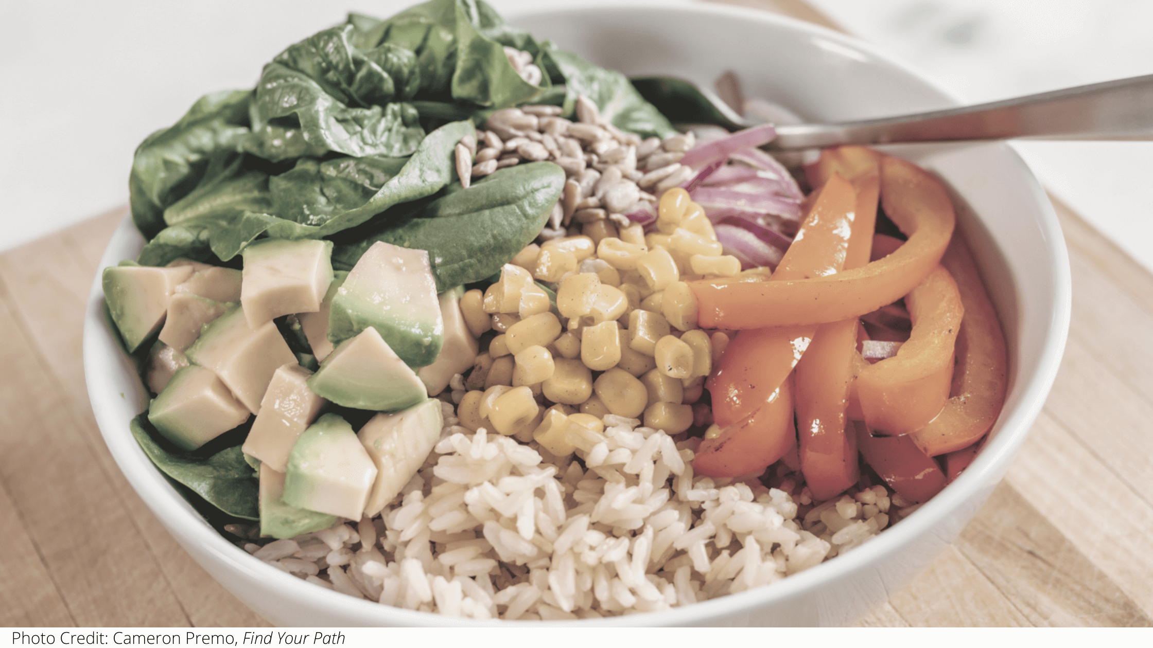 A delicious bowl of rice, avocado, peppers, corn, and more.