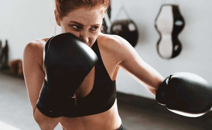 A red-headed woman wearing boxing gloves draws her arm into a punch.