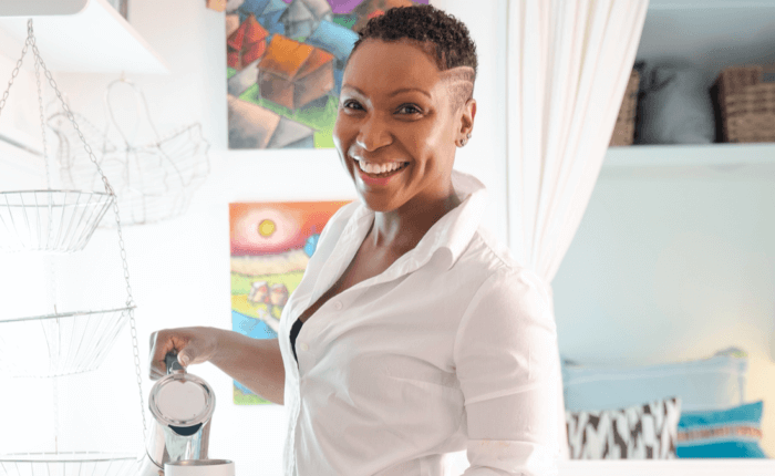 Trudie is all-smiles in her kitchen as she pours herself a cup of coffee