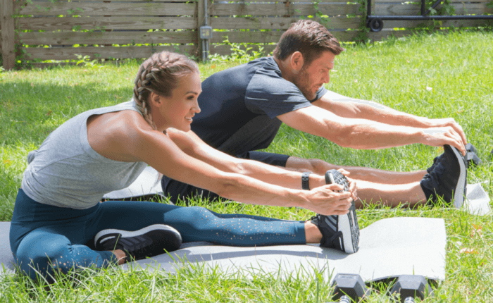 Carrie Underwood and Mike Fisher stretch before a personalized workout