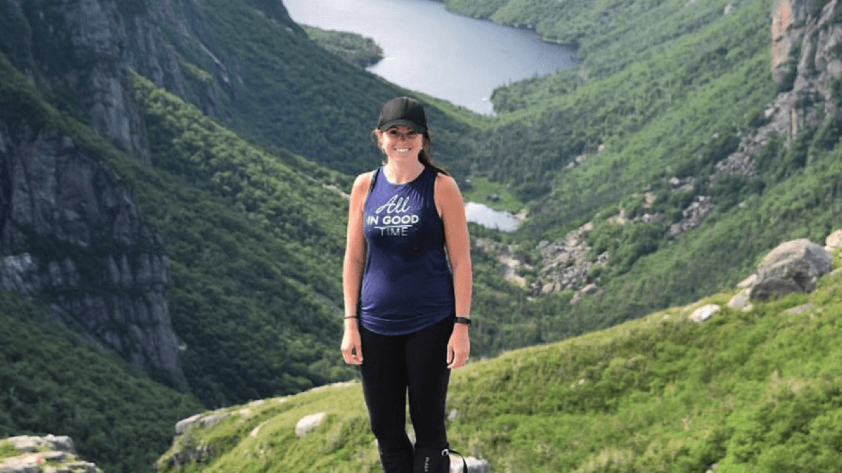 Courtney Clark, our wellness success story, stands on the top of a mountain