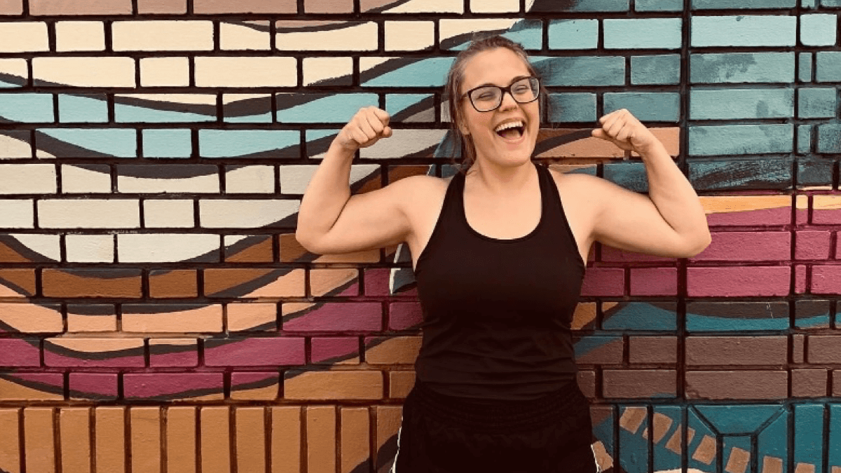Ally flexes in front of a mosaic wall with a big smile