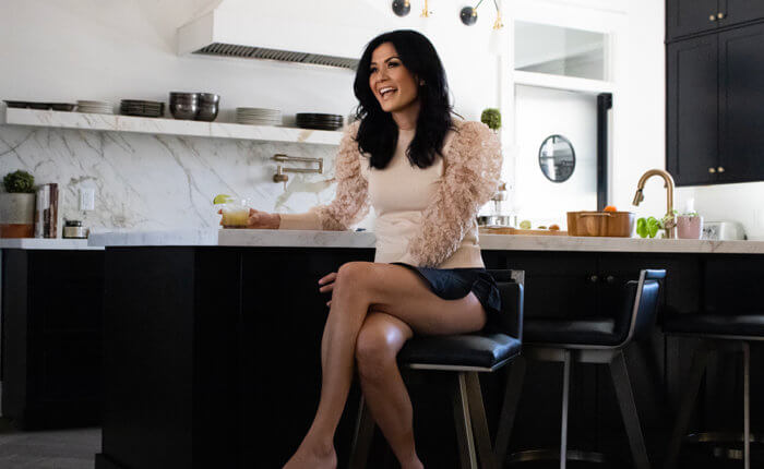 Ivey Childer sits at her kitchen island with a big smile on her face. Legs crossed, she holds a drink in her right hand.